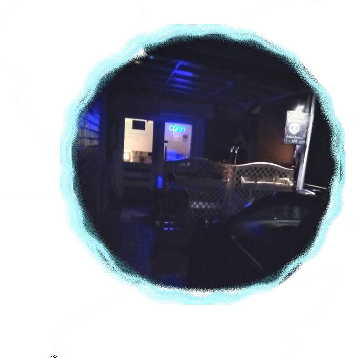 Eingangsbereich bei Nacht mit beleuchtetem blauen OPEN Schild